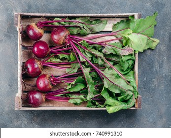 Beet, beetroot bunch in wooden box on dark stone or concrete background. Fresh ripe beetroot with leaf on dark table.. Top view or flat lay