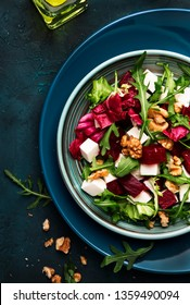 Beet or beetroot salad with fresh arugula, radicchio, soft cheese and walnuts on plate with fork, dressing and spices on blue kitchen table background, copy space, top view