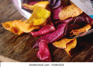 Beet and carrot salty chips in the bag from the store. Wooden  background.