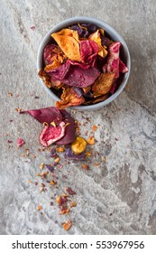 Beet and carrot salty chips in an old blue plate. Stone background.