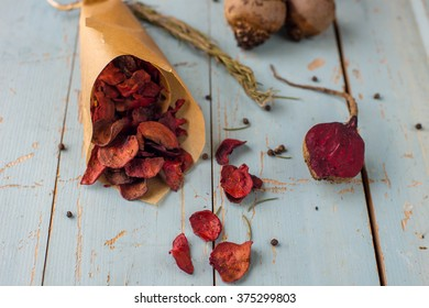The beet chips with rosemary on a blue wooden background