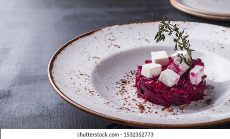 Beet salad with prunes and cheese on a plate. Copy space