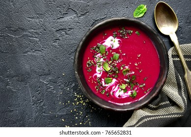 Beetroot creamy soup in a dark clay bowl over black slate,stone or concrete background.Top view with copy space.