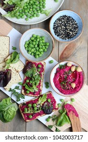 Beetroot hummus with sweet peas, baby lettuces, coriander leaves, sesame seeds and sesame and olive oils over corn tortillas. Top view, wooden surface