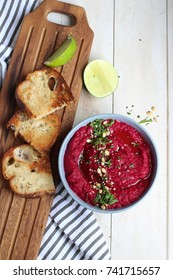 Beetroot humus with chickpea, sesame seeds and healthy chips over wooden surface