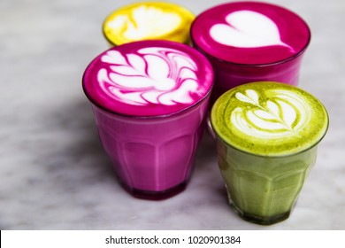 Beetroot, matcha,turmeric lattes are on the marble table with art floor on the background, Trendy healthy antioxydant drinks