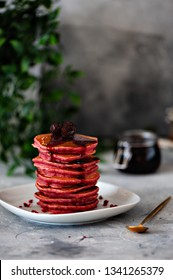 Beetroot pancake with cherry jam, on a gray background. Selective focus.