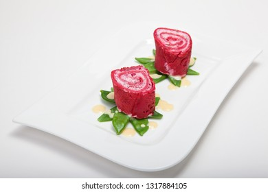 Beetroot pancake rolls stuffed with cream cheese on sugar snap peas with orange sauce on a white plate on a light background