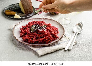 beetroot risotto with hard cheese, caramelized leaves,  dark black background