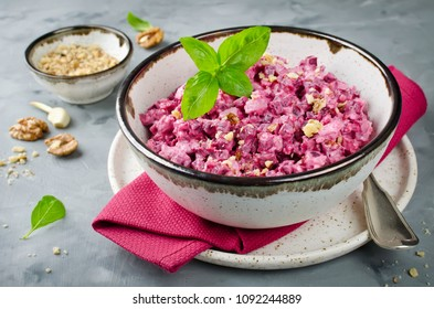 Beetroot salad with chicken and walnut in a ceramic bowl. Delicious balanced food concept
