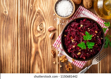 Beetroot salad with wallnuts and garlic in bowl on wooden table. Top view. Copy space.