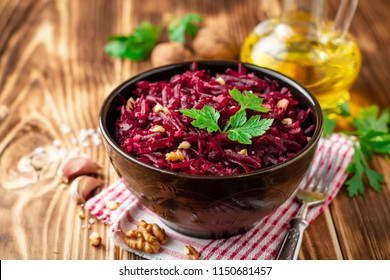Beetroot salad with wallnuts and garlic in bowl on wooden table. Selective focus.