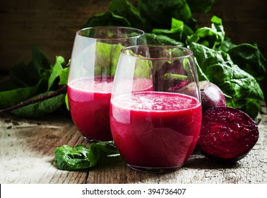 Beetroot smoothie in a large glass, fresh beets with tops, old wooden background, selective focus