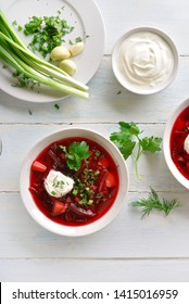 Beetroot soup in bowl on white wooden table. Traditional ukrainian russian soup (borscht) with greens and sour cream. Top view, flat lay