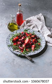 Beetroot and strawberry salad served with arugula and nuts on ceramic plate with cloth and bottles of fruit ocet and olive oil over grey texture background. Healthy eating