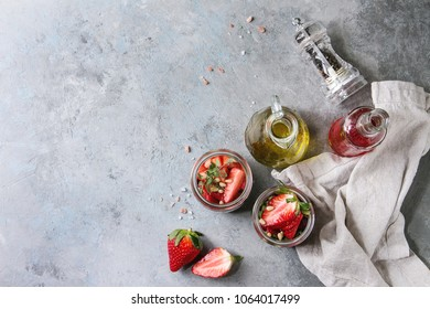 Beetroot and strawberry salad served with arugula and nuts in glass jars with cloth and bottles of fruit ocet and olive oil over grey texture background. Top view, space. Healthy eating