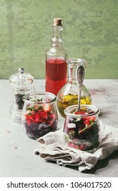 Beetroot and strawberry salad served with arugula and nuts in glass jars with cloth, pepper and bottles of fruit ocet and olive oil over grey table with green wall as background. Toned image