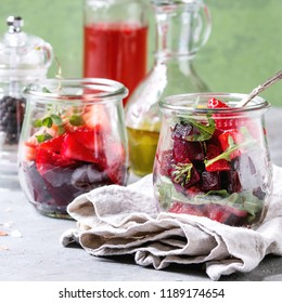 Beetroot and strawberry salad served with arugula and nuts in glass jars with cloth, pepper and bottles of fruit ocet and olive oil over grey table with green wall as background. Square image