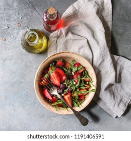 Beetroot and strawberry salad served with arugula and nuts on ceramic bowl with cloth and bottles of fruit ocet and olive oil over grey texture background. Top view, copy space. Square images