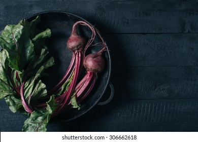 Beets with green tops in a black iron pan on a black wooden background
