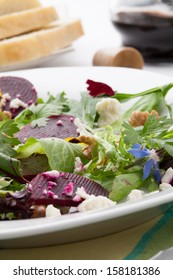 Beets with walnuts, goat cheese, and baby greens organic salad.