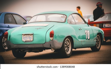 Beeville, Texas USA 03-22-2013 Volkswagon Karmann Ghia race car in unique color  on the starting grid at a race track. Contemporary edit.