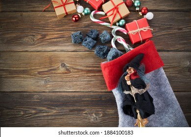 The Befana with sweet coal and candy on wooden background. Italian Epiphany day tradition.