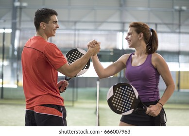 Before or after macth, couple hi five in paddle tennis court