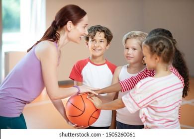 Before basketball game. PE teacher and children smiling before starting basketball game at PE class