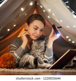 Before bedtime. A girl with a Scottish and British cat reading a book in a tent. A concept of rest, fairy tales, night, sleep and warmth, dreams