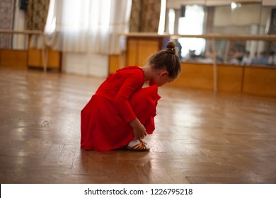 Before the dance lesson. The little girl in the red training costume (dress) and ballroom dance training shoes.