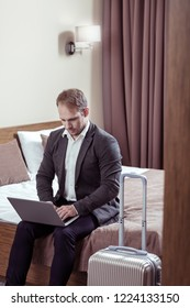 Before leaving. Busy successful businessman working on his laptop before leaving hotel room