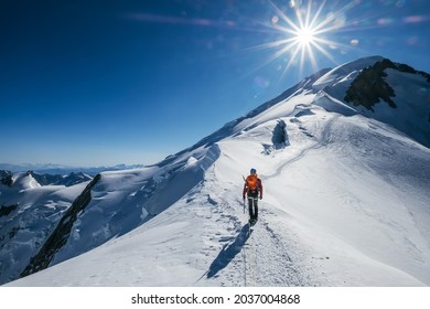 Before Mont Blanc (Monte Bianco) summit 4808m last ascending. Team roping up Man with climbing axe dressed high altitude mountaineering clothes with backpack walking by snowy slopes with blue sky.
