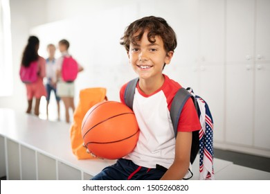 Before PE class. Cheerful schoolboy holding basketball ball feeling excited before PE class