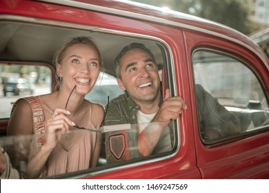 Before walking. Cheerful married couple sitting next to each other on the car backseat and looking out of the window.