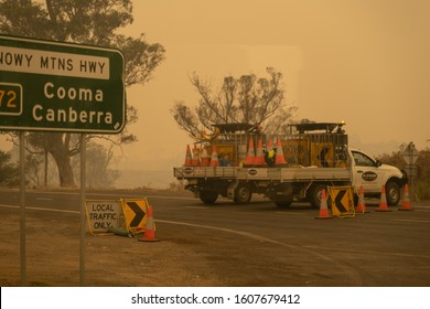 Bega, Australia - January 1, 2020: Emergency responders closed roads due to bushfires as thick orange haze envelopes Snowy Mountains Highway. Personnel standing at closed intersection in Bega, NSW.