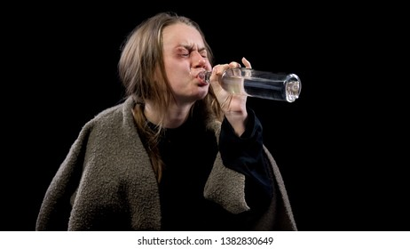 Beggar crying in despair drinking vodka, helpless in poverty, alcohol addiction