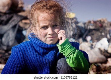 Beggar, a hungry child sitting tired of hard work in a garbage dump close up