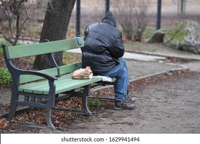 A beggar on a bench in a park in Berlin-Germany. An old, homeless man sits on a bench on a cold winter day.
