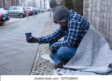 Beggar's Hand Wearing Gloves Holding Disposable Cup