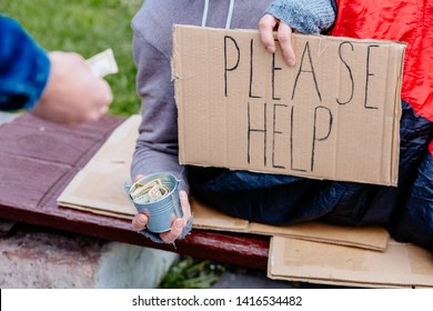"""Beggar's Hand Wearing Gloves Holding Homeless Placard With Text """"Please Help"""" begging money , outdoor. Unrecognizable man giving dollar bill money to beggar homeless. Poverty and social issue concept."""