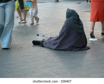 Begging woman with people walking by in the streets of Barcelona, Spain