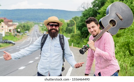 Begin adventure. Travelers with backpack and guitar ready to strat new journey. Men at edge of road hitchhiking. Friends gathered travel together. Men travelling by hitchhiking. Hitchhiking partner.