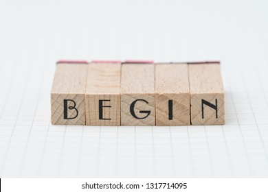 Begin, debut, company establish or start own business concept, wooden stamp with alphabet building the word BEGIN on grid line note book paper.