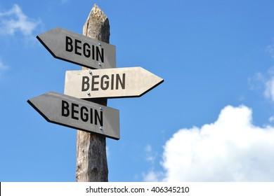 """Begin, begin, begin"" - wooden signpost, cloudy sky"