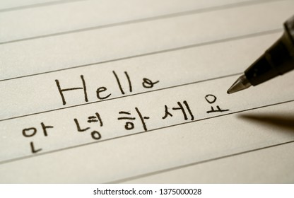 Beginner Korean language learner writing Hello word Annyeonghaseyo in Korean characters on a notebook close-up shot