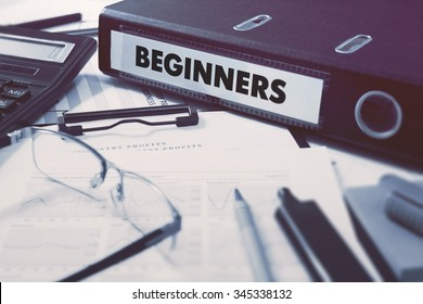 Beginners - Office Folder on Background of Working Table with Stationery, Glasses, Reports. Business Concept on Blurred Background. Toned Image.