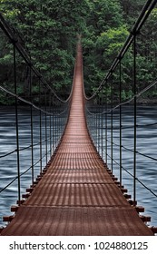 Beginning of an adventure, road into the jungle. Suspension bridge. Landscape view of Long Steel Suspension bridge above the river. balance