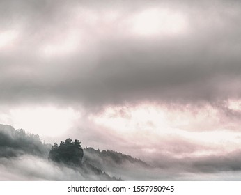Beginning of autumn. Fantastic dreamy misty  sunrise above deep valley hidden in the rocky mountains . Beautiful fall misty day
