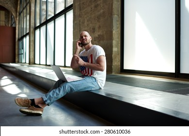 Beginning business man sitting in new premise for rent or empty work space talking on mobile phone,male interior designer or young architect sitting in empty office working on a laptop and smart phone